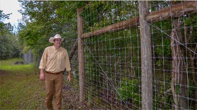 Jon next to a high fence
