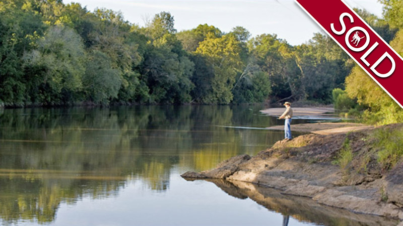 Man fishing on river bank